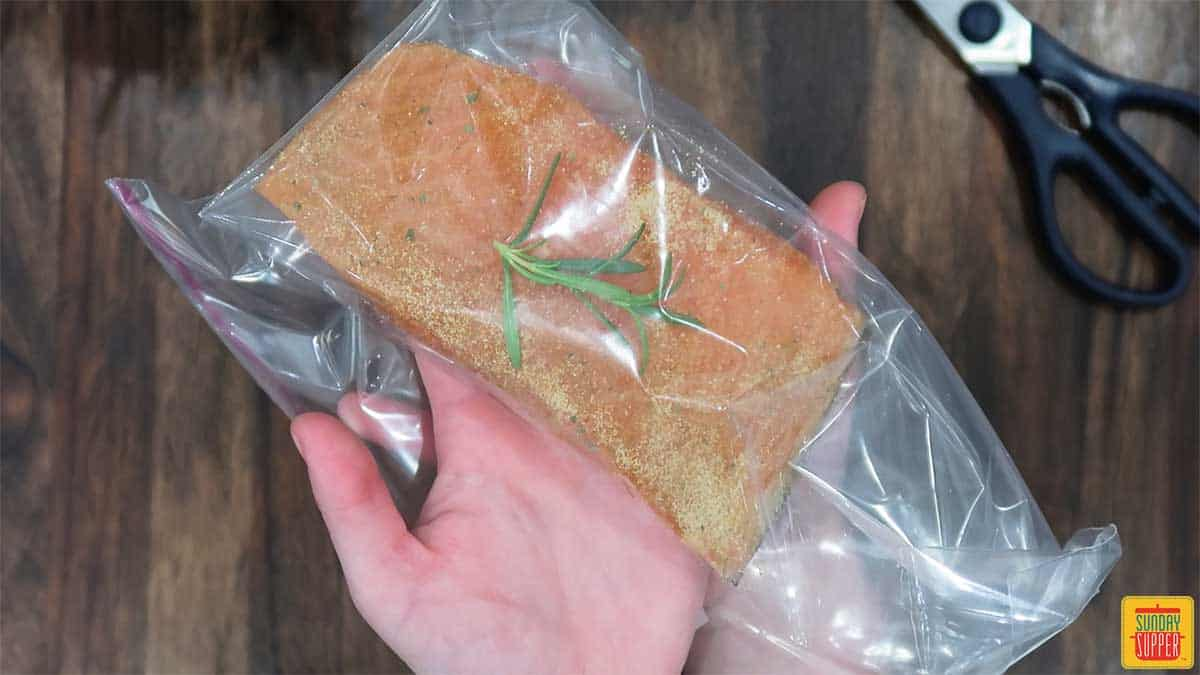 Seasoned salmon in a plastic bag with a rosemary sprig on top