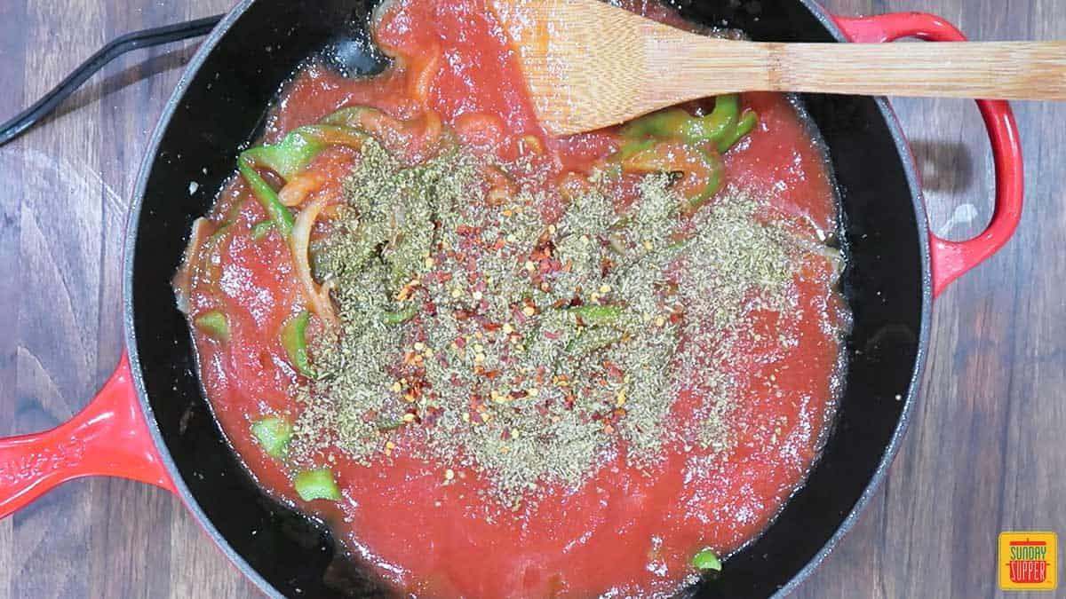 Adding seasoning to steak pizzaiola sauce