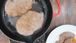 Browned steaks in a skillet for steak pizzaiola