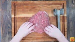 Seasoned tenderized steak on a cutting board