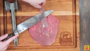Cutting the silver skin away from a tenderized steak