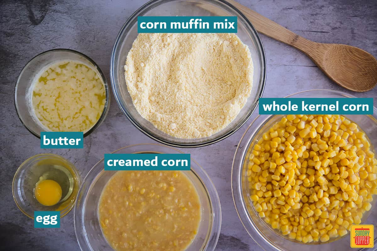ingredients for baked creamed corn casserole in bowls with labels