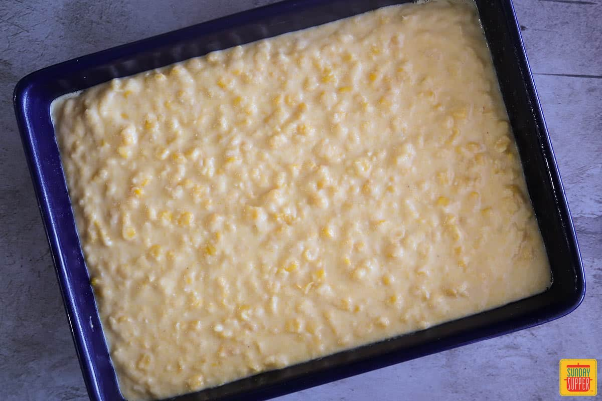 Creamed corn casserole spread out into a blue baking dish unbaked
