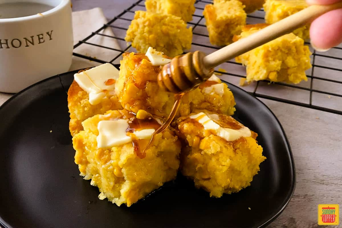 drizzling honey on top of cornbread with pats of butter