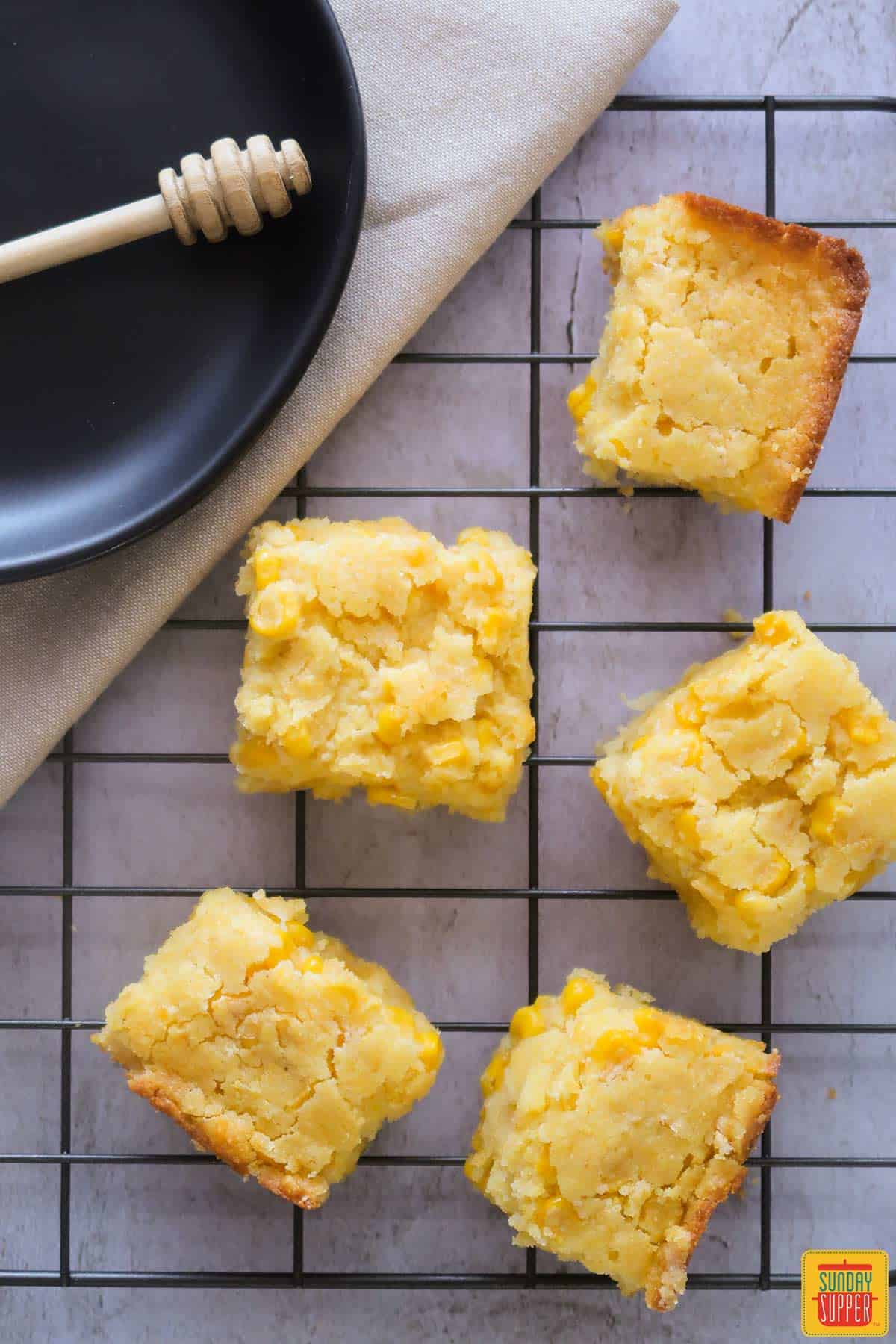 Squares of creamed corn casserole on a rack