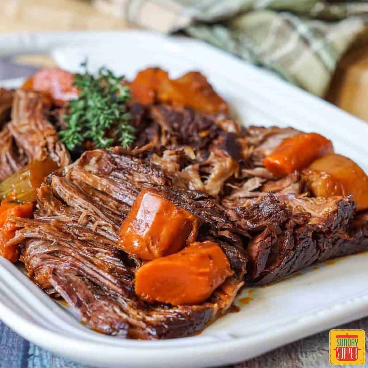 Beef chuck roast on a white plate with carrots and herbs