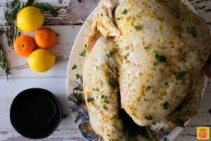 Seasoned turkey rubbed with butter and stuffed with citrus on a platter