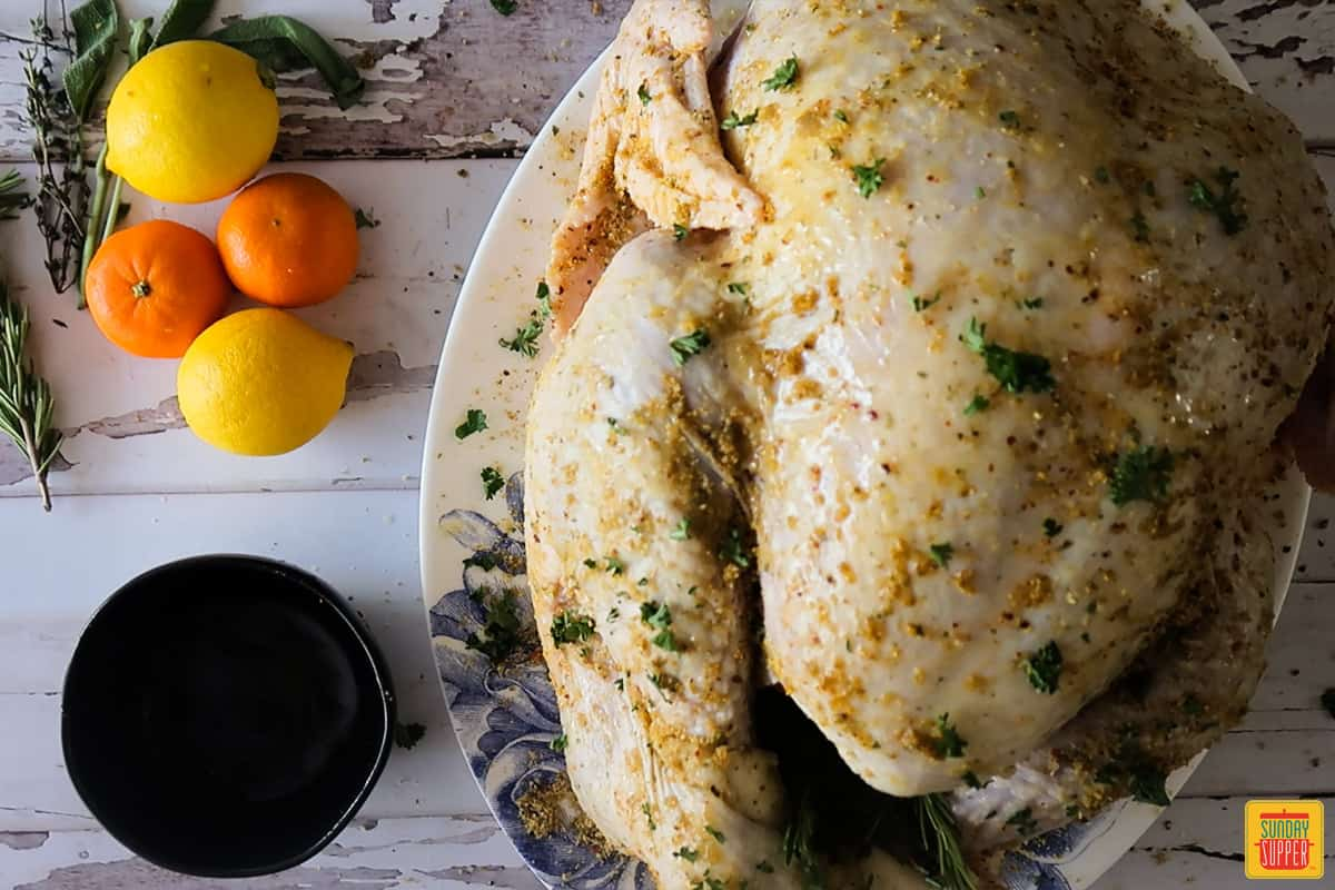 Uncooked seasoned turkey rubbed with butter and stuffed with citrus and herbs on a platter