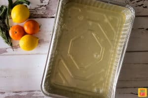 Chicken broth in a pan on a white surface next to lemons and clementines