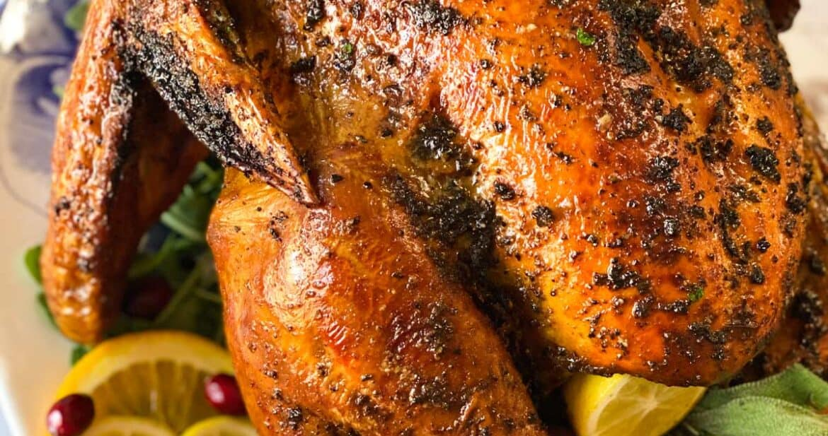 Close up of grilled turkey on a platter with citrus and herbs