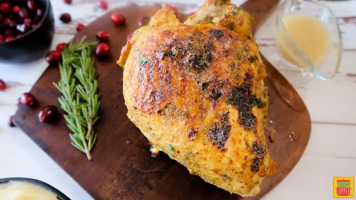 cooked turkey breast on a cutting board with a sprig of rosemary and cranberries