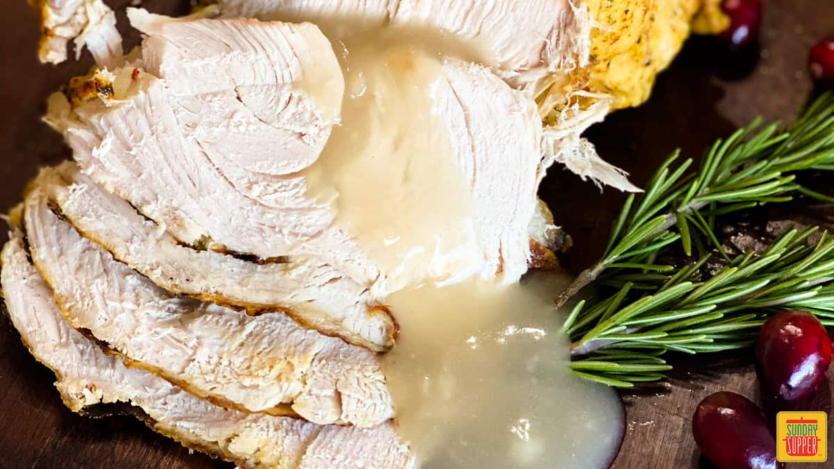 Gravy over sliced turkey breast next to rosemary sprigs and cranberries