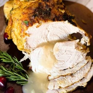 Slices of instant pot turkey breast covered with gravy and rosemary sprigs to the side