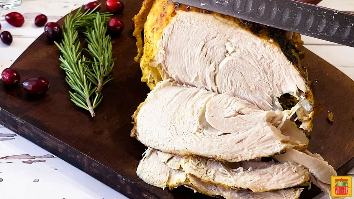 Slicing instant pot turkey breast on a cutting board