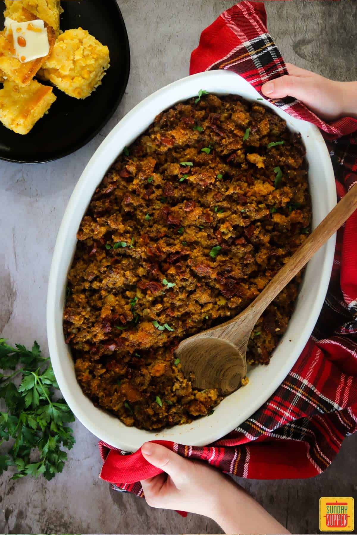 Holding a white dish with Portuguese chorizo cornbread stuffing next to a plate of fresh cornbread