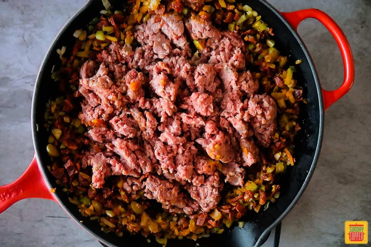 Ground beef added to the center of the pan surrounded by chorizo and vegetables