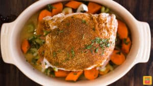 Turkey roast seasoned with parsley over celery and carrots