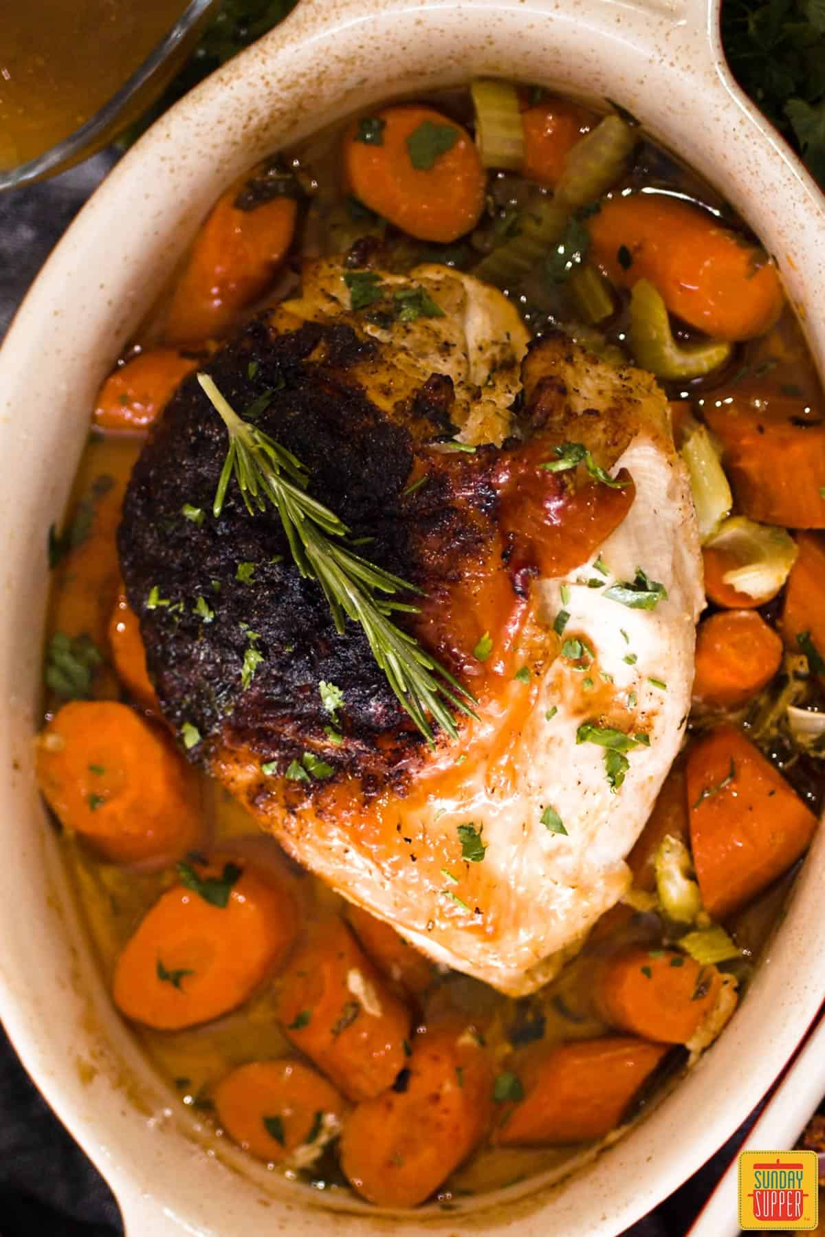 Roast turkey breast over carrots and celery in a baking dish
