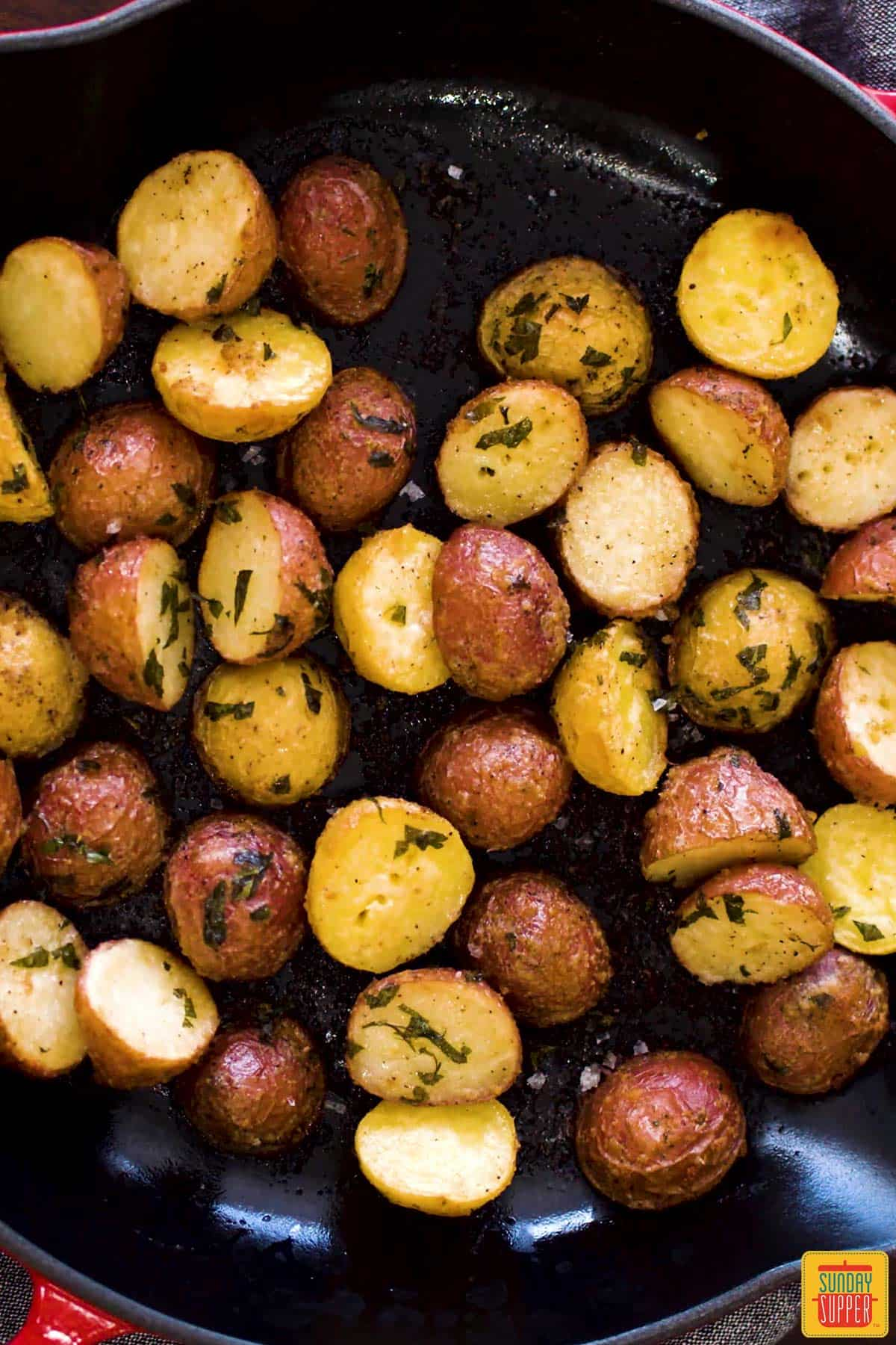 Close up of garlic roasted small potatoes in a skillet