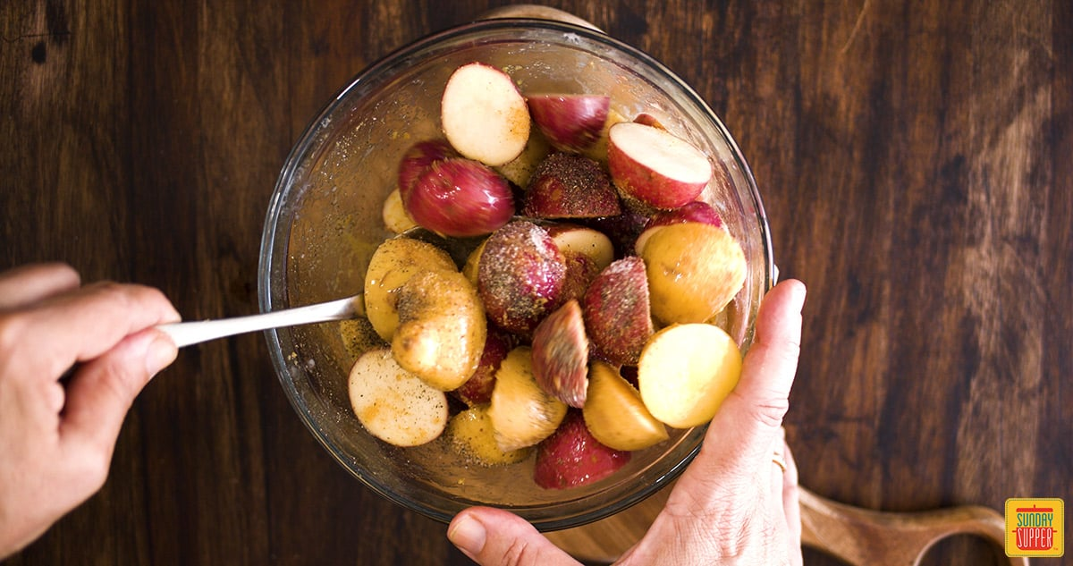 Mixing creamer potatoes with seasoning in a glass bowl