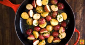 Uncooked small potatoes in a skillet with seasoning and parsley
