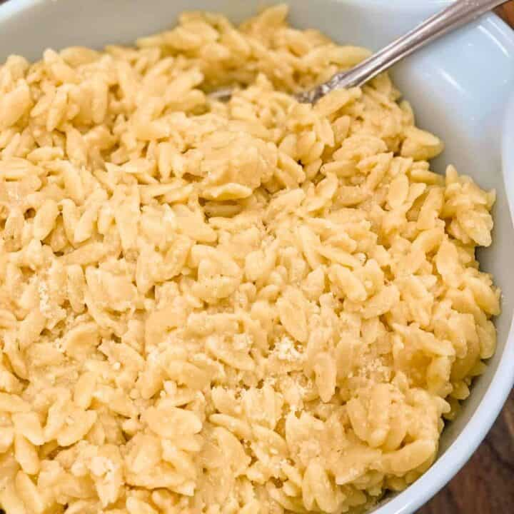 Close up of cheesy orzo in a white bowl