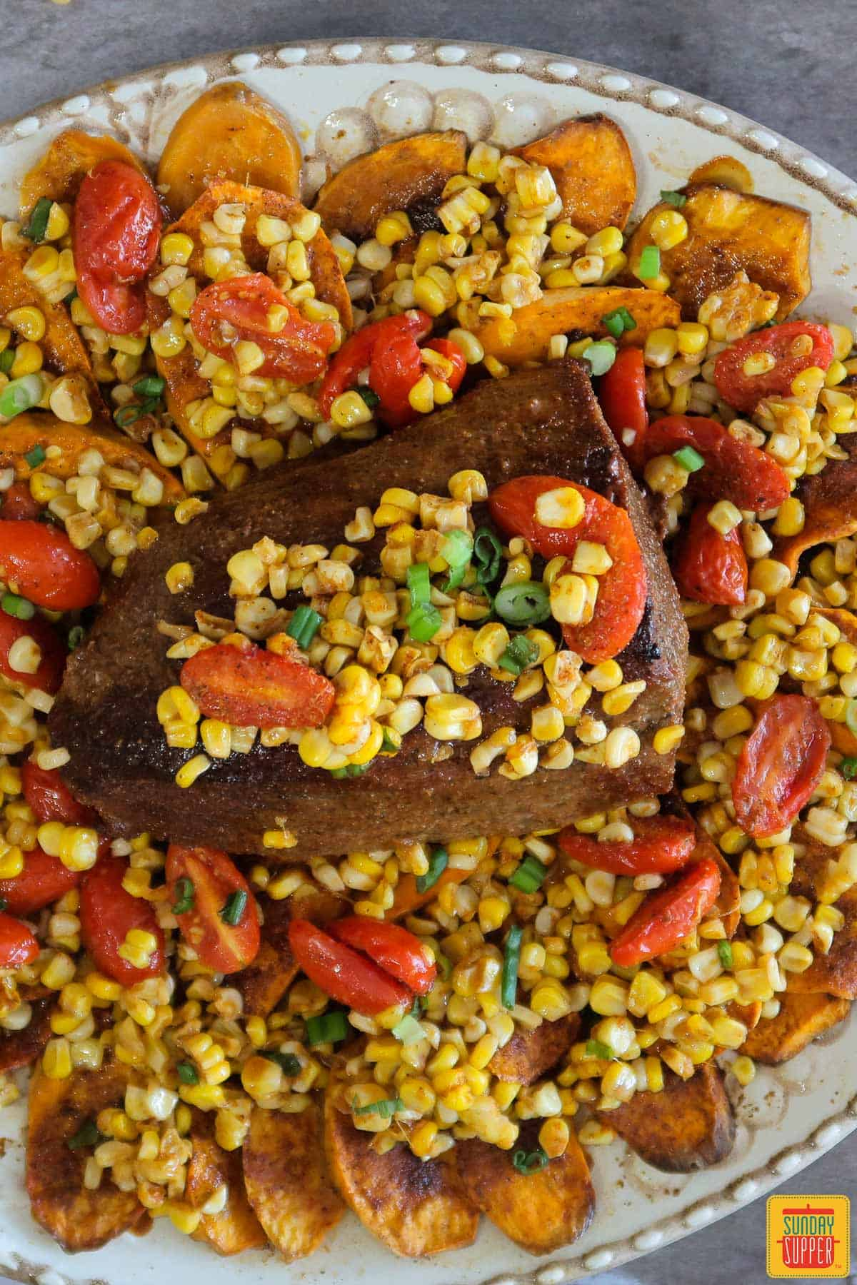 Corn and tomatoes on top of eye of round roast