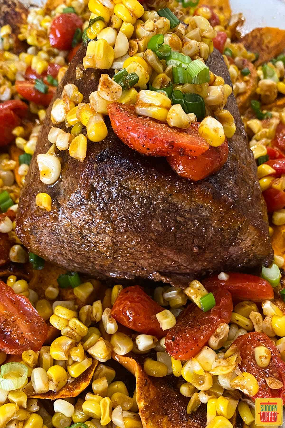 Close up on eye of round roast surrounded by corn, tomatoes, and sweet potatoes