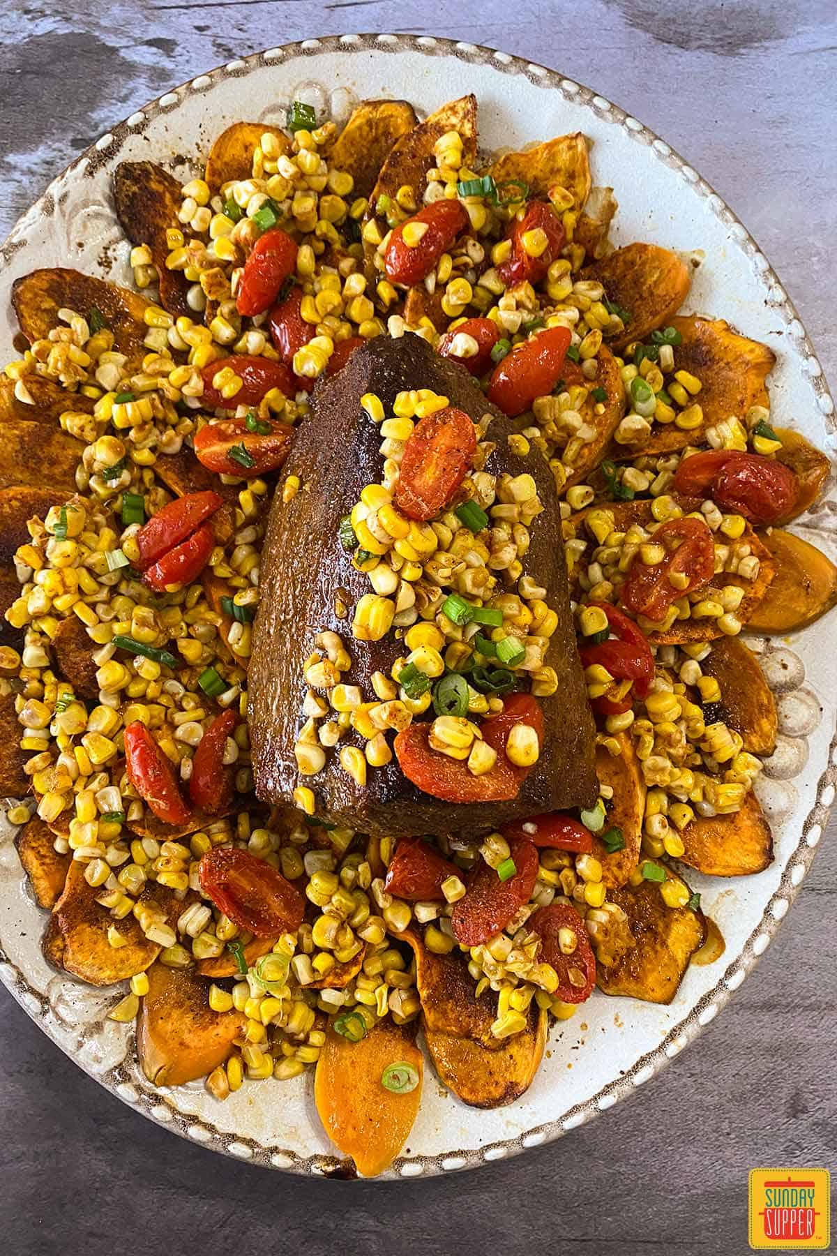 Overhead view of eye of round roast on a bed of sweet potatoes, corn, and tomatoes