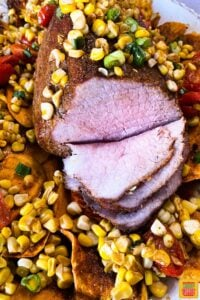 Sliced eye of round roast on a platter with sweet potatoes, corn, and tomatoes