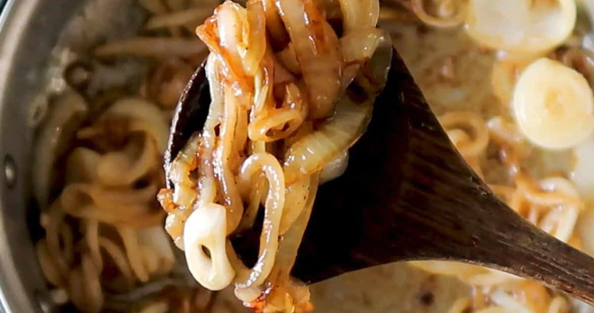 caramelized onions on a wooden spoon over a pan of onions