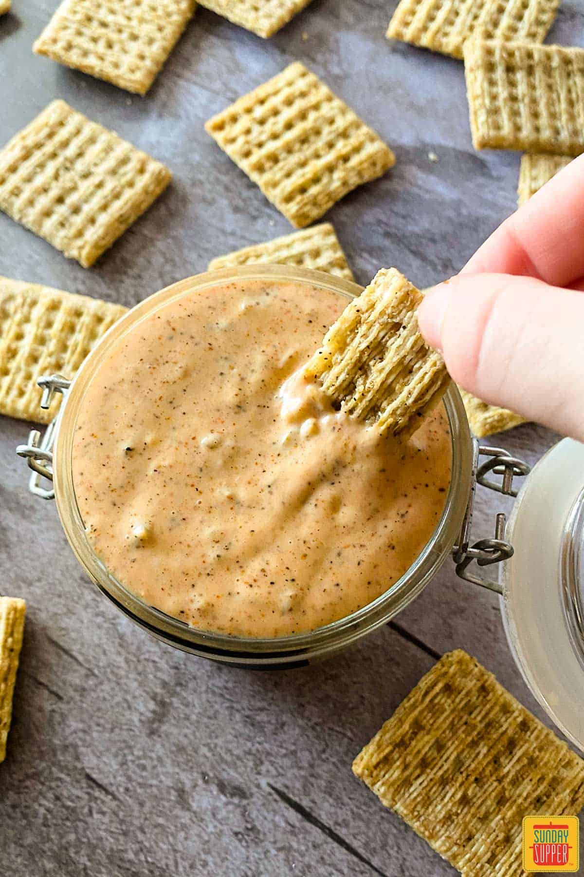 Dipping a cracker into remoulade sauce in a glass jar
