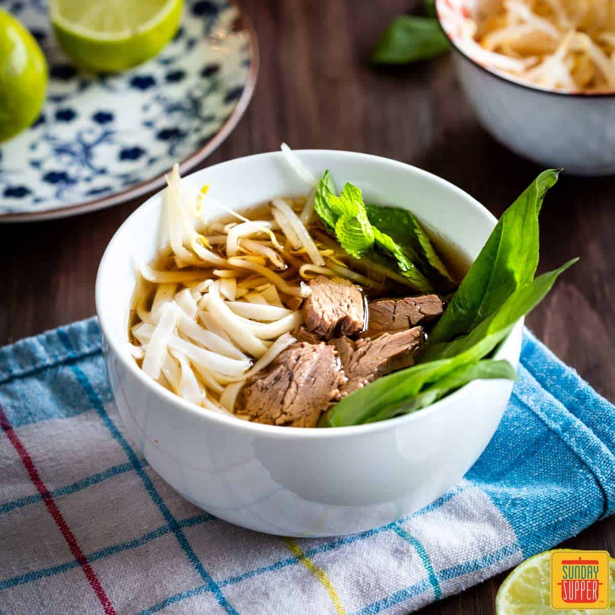 Instant Pot Pho in a white bowl with beef, rice noodles, and fresh herbs