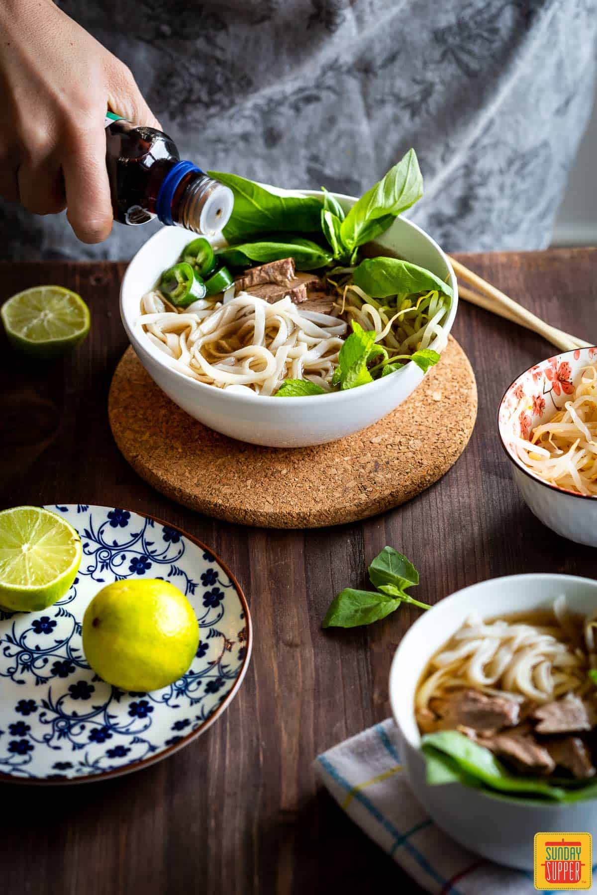 Adding soy sauce to pho