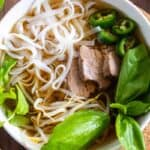Instant Pot Pho in a white bowl with beef and noodles