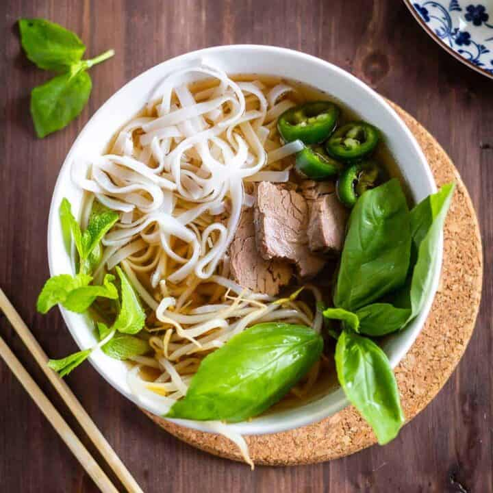 Beef pho in a white bowl with basil and noodles