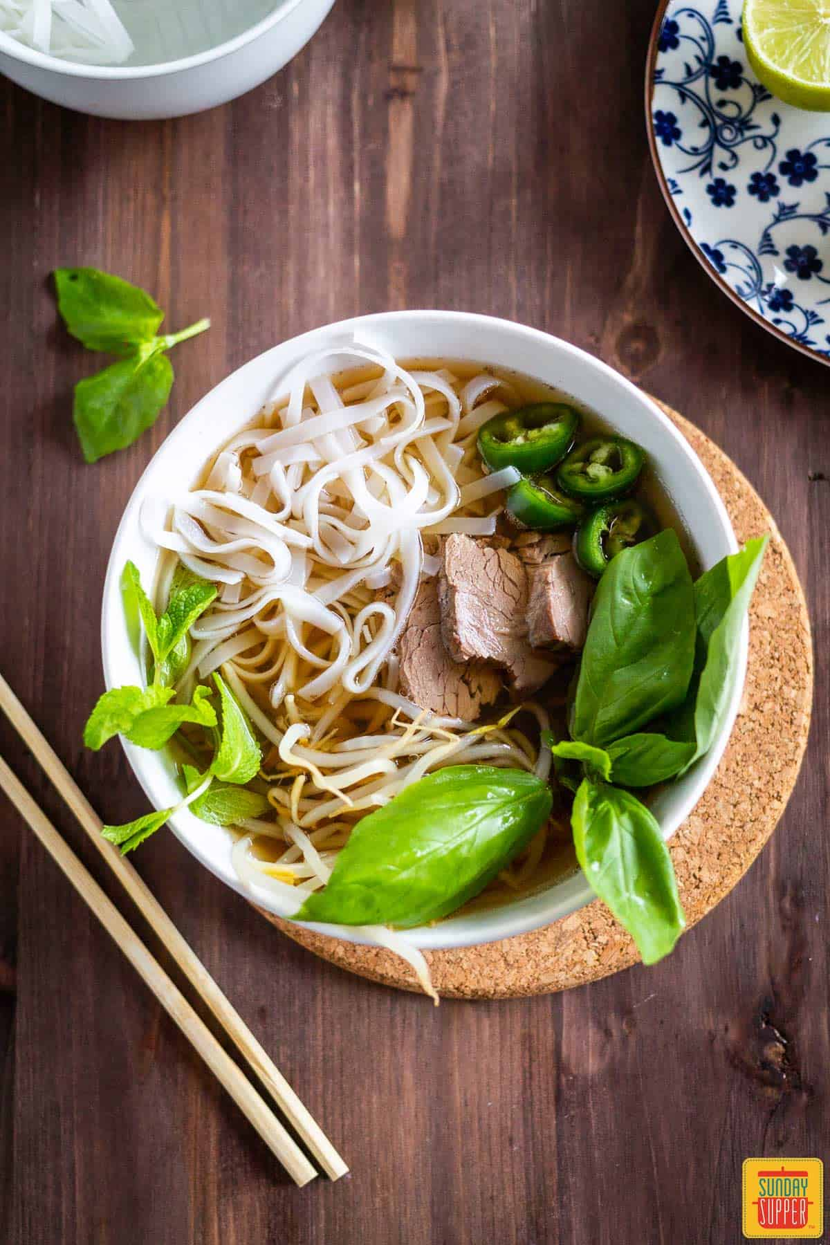 Instant Pot beef Pho in a white bowl with basil and chopsticks