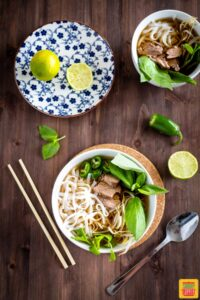 Instant pot pho in two bowls with citrus to the side