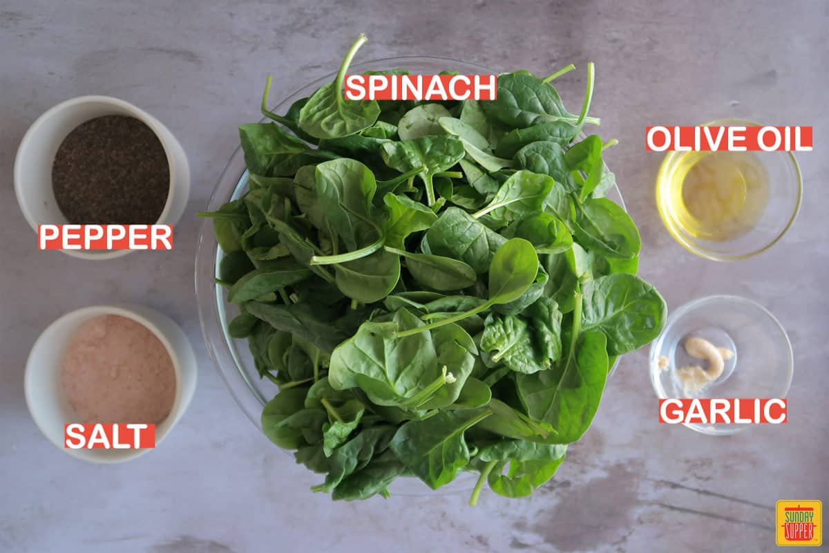 Ingredients for sauteed spinach labeled on a table