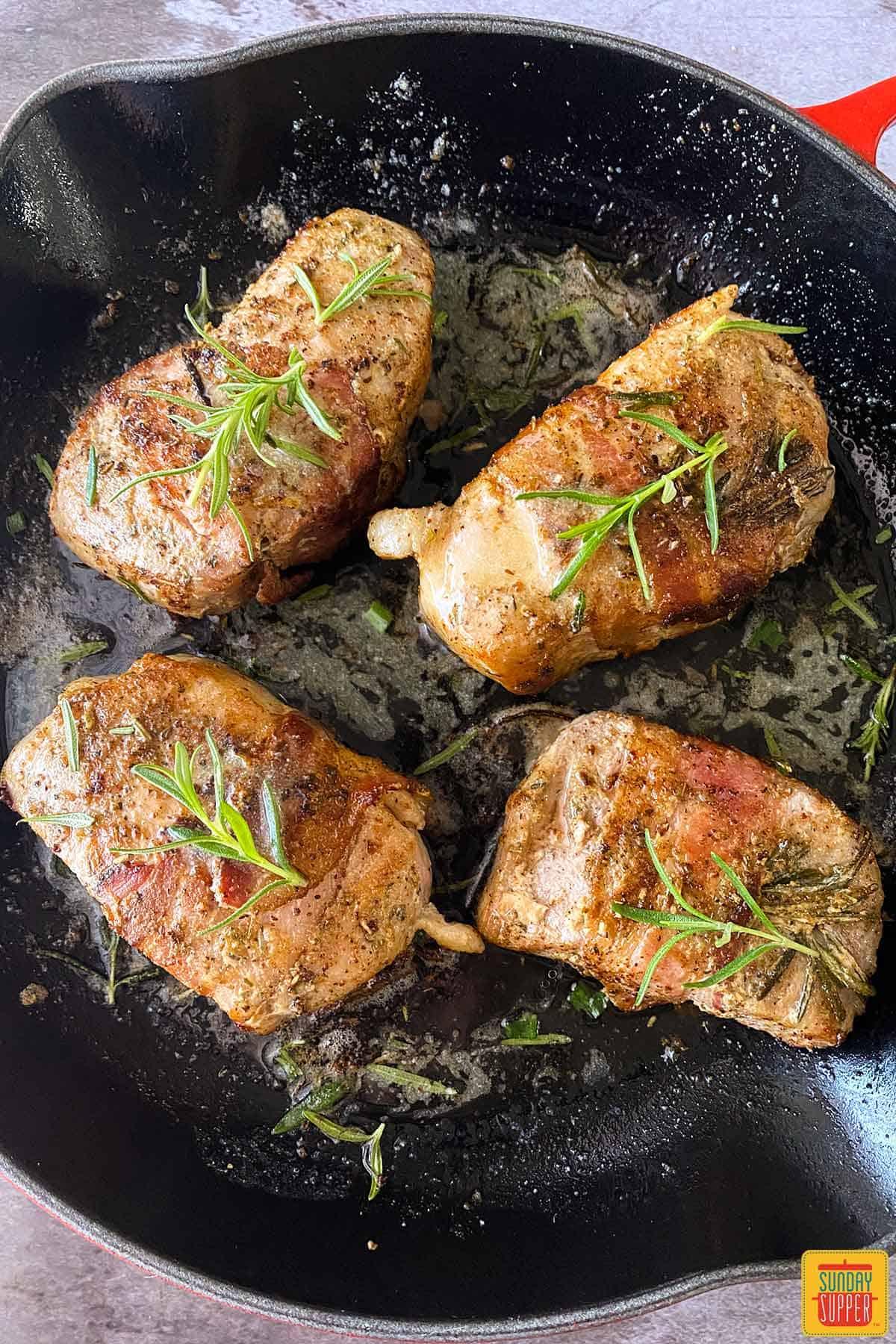 Four sous vide pork chops in a skillet