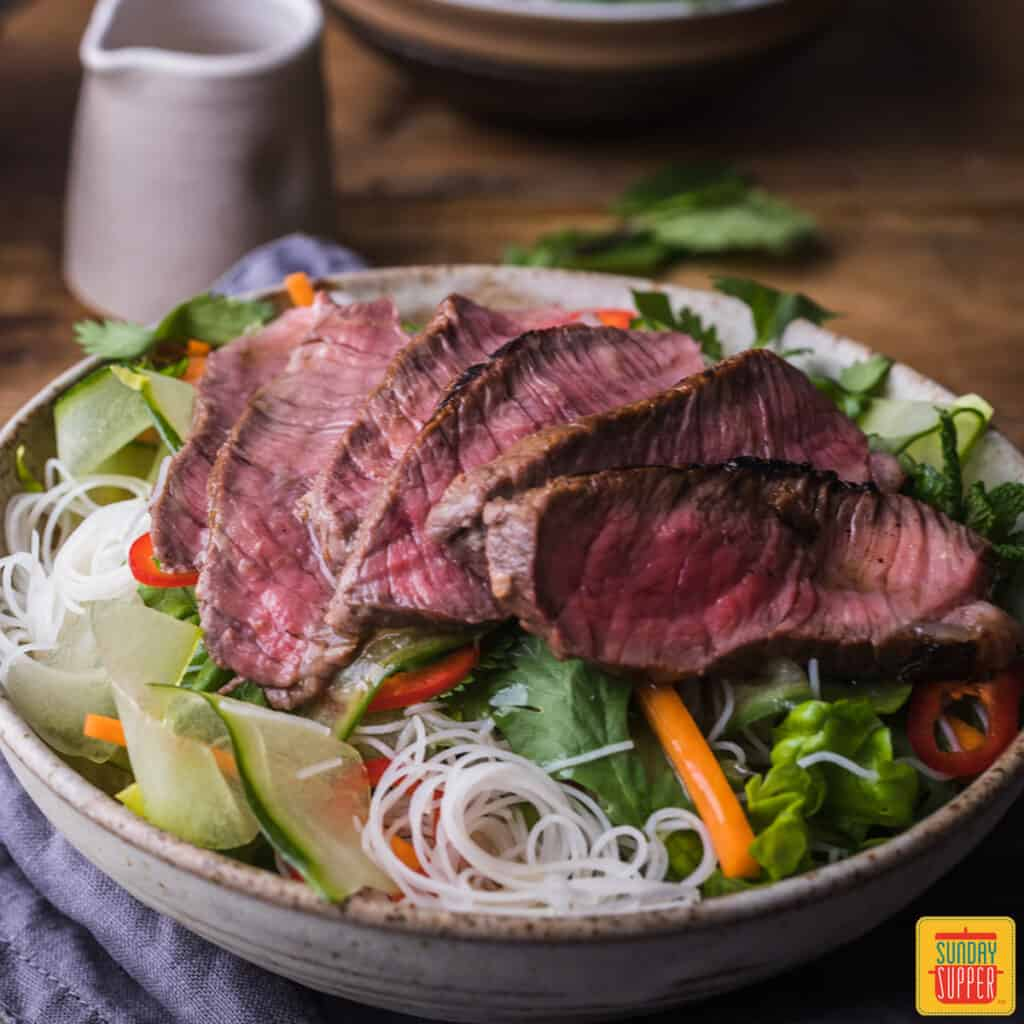 Slices of sirloin steak over rice noodles and vegetables