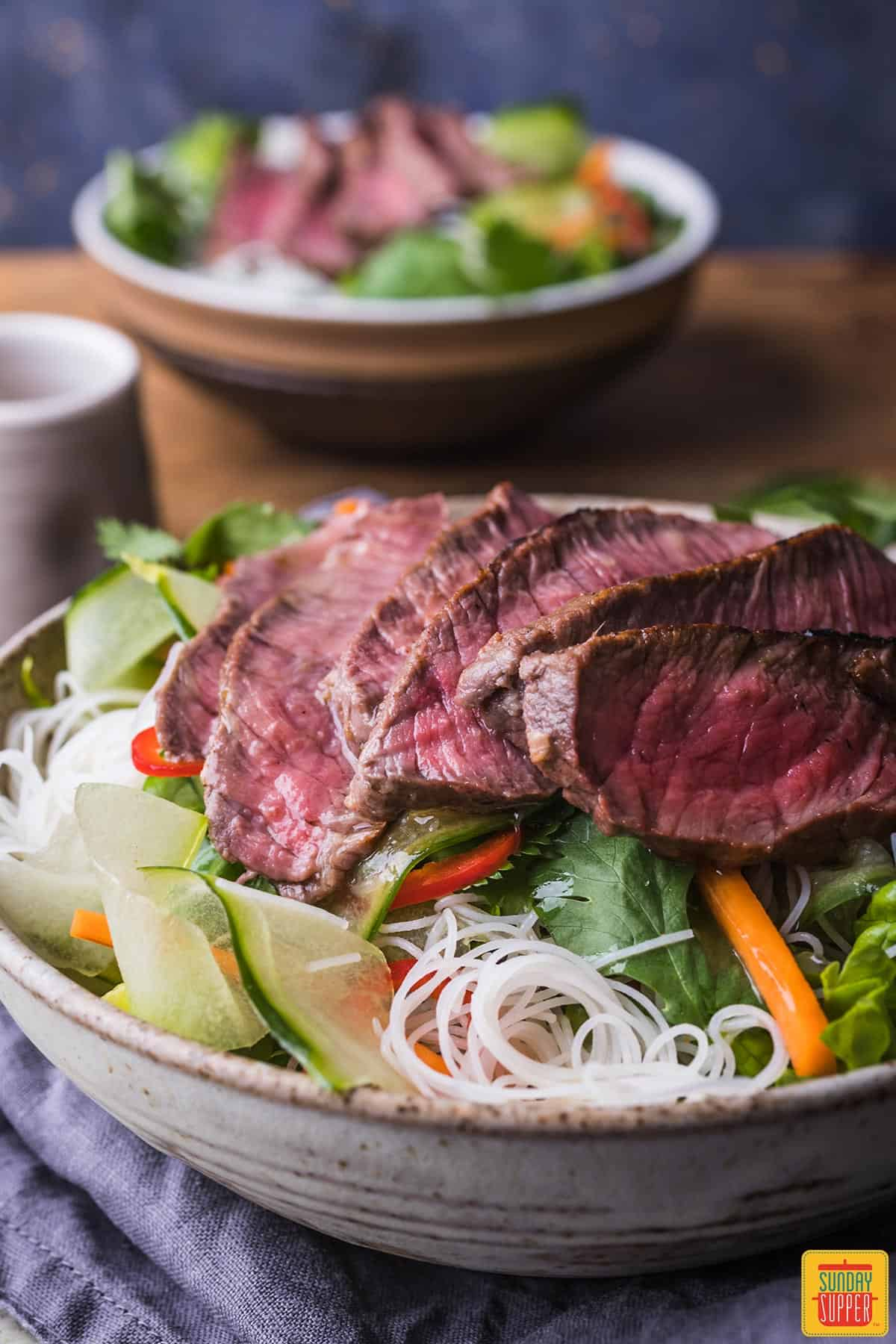 Sirloin steak sliced thinly over rice noodles and crisp veggies in a bowl
