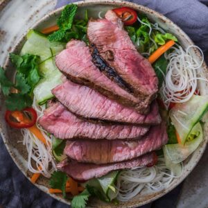 Top-down view of vietnamese steak salad with sirloin and rice noodles