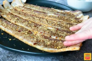 Patting candied bacon mixture onto bacon