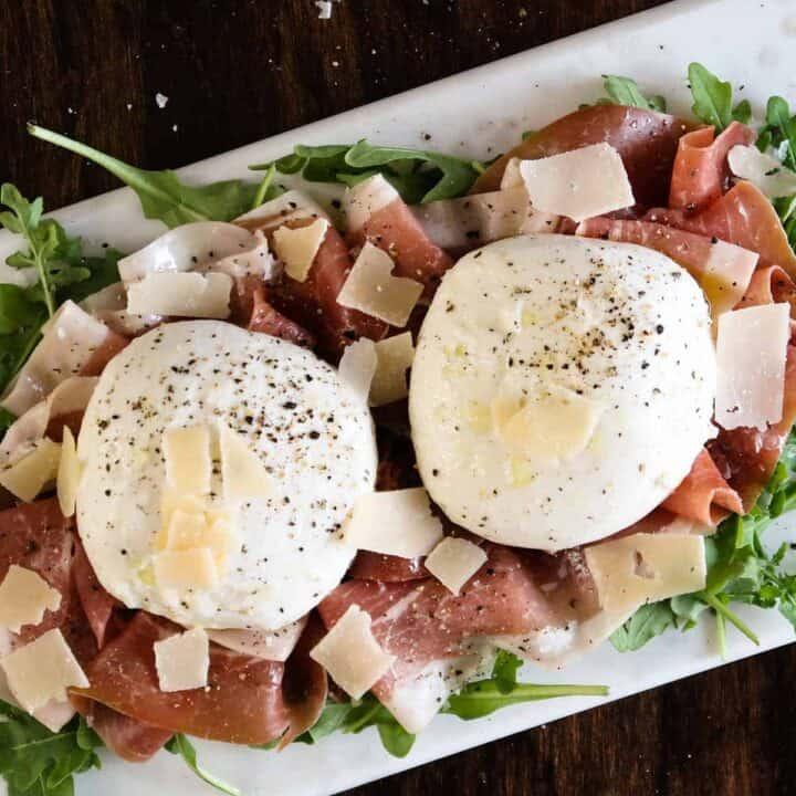 Burrata cheese topped with parmesan on a bed of prosciutto and arugula with olive oil