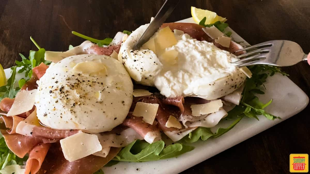 Cutting open burrata with a knife and fork over salad
