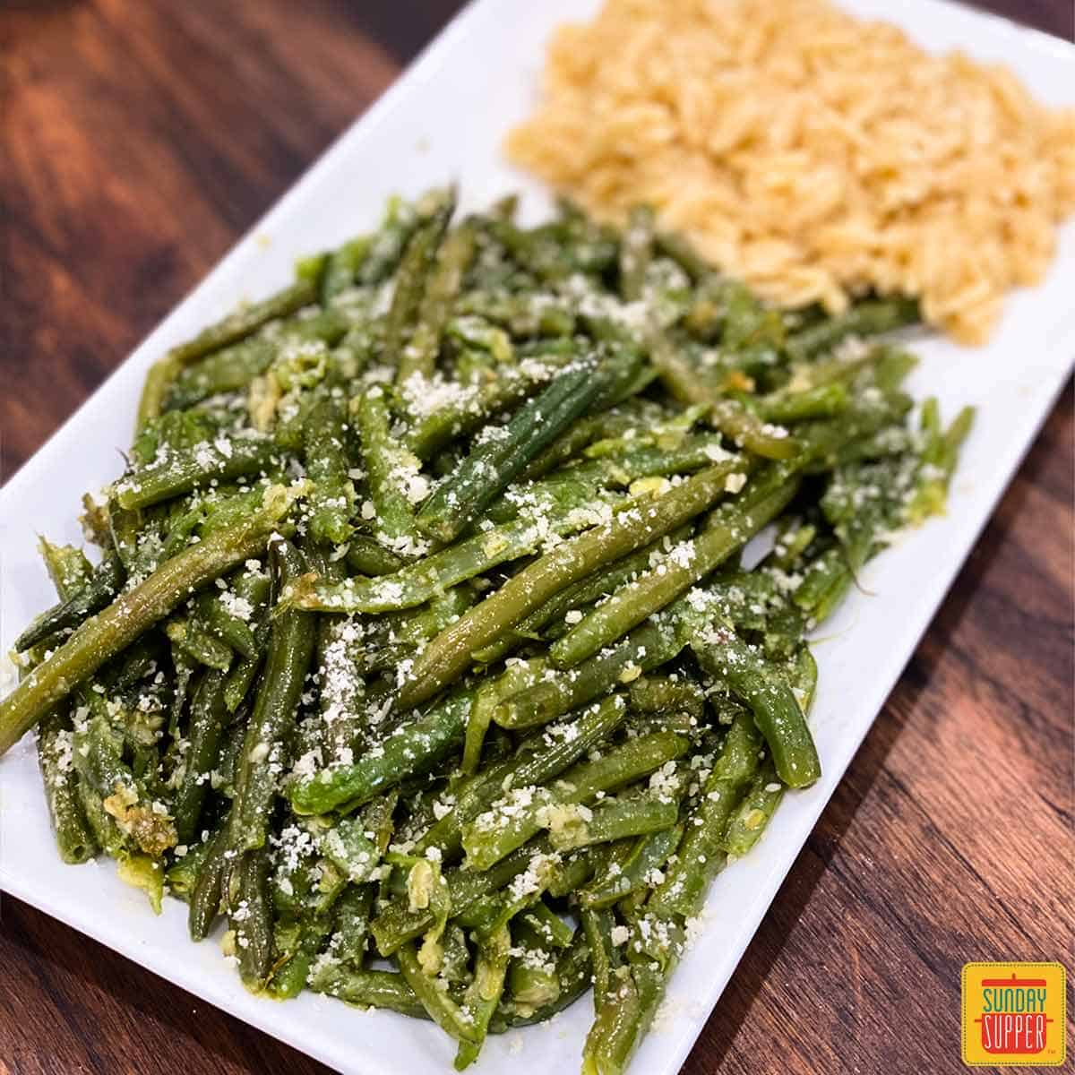 Instant pot garlic butter green beans on a white plate with orzo to the side