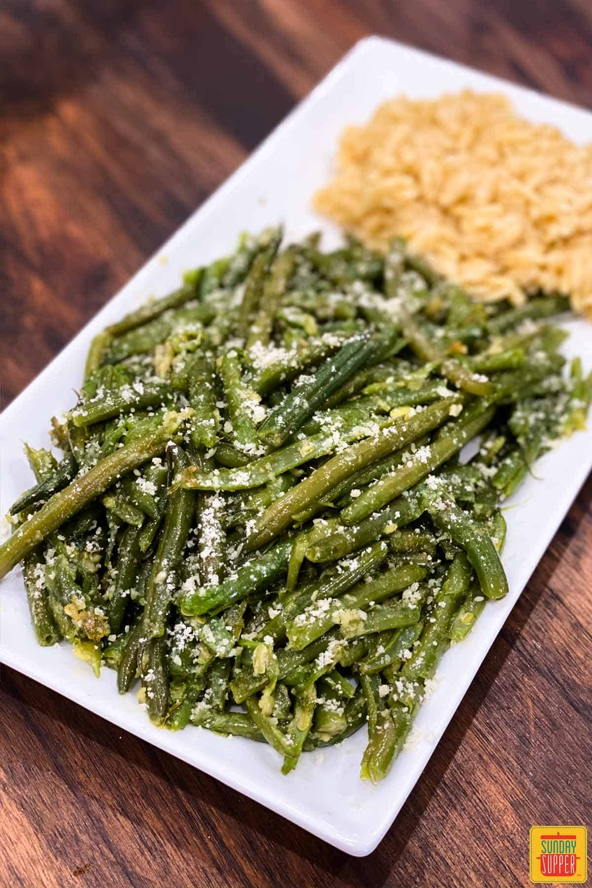 Green beans on a plate with orzo and parmesan
