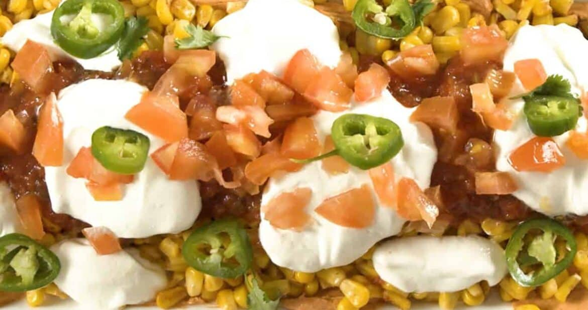 Taco dip on a white plate with tomatoes and jalapenos on top