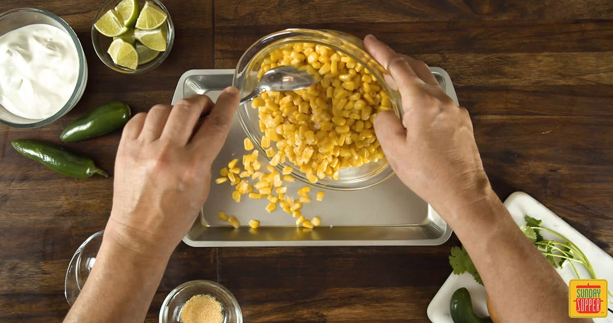 Pouring corn kernels into a dish
